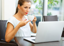 Attractive business woman sitting in a cafe with a laptop and dr Royalty Free Stock Photo