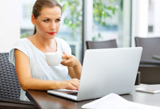 Attractive business woman sitting in a cafe with a laptop and dr Stock Image