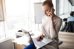 Attractive business woman is sitting at the edge of table and holding a laptop on her knees. She is looking at it. Also. Woman is talking on the phone. She is royalty free stock photos