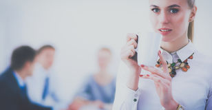 Attractive business woman sitting at office desk, holding a cup of coffee Royalty Free Stock Photos
