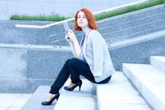 Attractive business woman sitting on the street with a tablet on a sunny day Stock Image