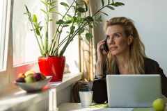 Attractive business woman sitting at table with laptop talking on the phone. Stock Photo