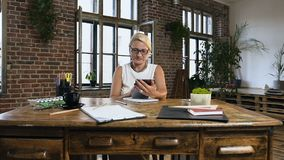 Attractive business woman sitting at table is typing on the tablet during work time in the modern office stock video footage