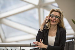 Attractive business woman speaks on a cell phone. Royalty Free Stock Photos