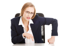Attractive business woman by the table, bossy behaviour. Royalty Free Stock Images