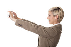 Attractive business woman takes a self portrait. Beautiful young woman photographs herself with a cell phone Royalty Free Stock Images