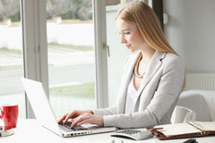 Attractive business woman is typing on her keyboard Stock Photography