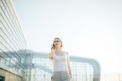 Business woman using a phone and clock while standing in outdoor. Attractive business woman using a phone and clock while standing in front of windows in an Royalty Free Stock Photo