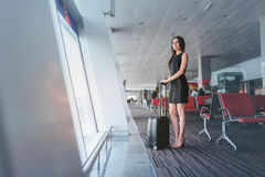 Attractive business woman is waiting for her flight with smile. Ready to discover. Charming elegant girl is standing with suitcase and looking at airplanes royalty free stock photography