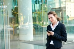 Attractive business woman walking outside with mobile phone Stock Photography