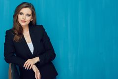 Attractive business woman wearing suit standing against blue wall royalty free stock photo