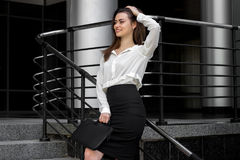 Attractive business woman in a white shirt and black skirt stands in the street Stock Photos