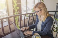 Attractive business woman is working on computer in a coffee sho stock photos