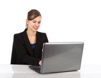 Attractive business woman working on a laptop. Computer against a white background Stock Image