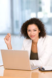 Attractive business woman working on laptop.  Royalty Free Stock Photography