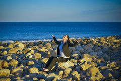 Attractive business woman working on laptop at beach. Attractive business woman working on a laptop sitting on some rocks at the beach looking up to sky thinking Stock Photo