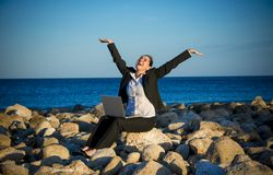 Attractive business woman working on laptop at beach. Attractive business woman working on a laptop sitting on some rocks at the beach looking up to sky thinking Royalty Free Stock Photos