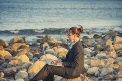 Attractive business woman working on laptop at beach. Attractive business woman working on a laptop sitting on some rocks at the beach looking up to sky thinking Royalty Free Stock Images