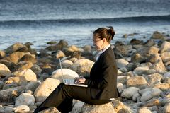 Attractive business woman working on laptop at beach. Attractive business woman working on a laptop sitting on some rocks at the beach looking up to sky thinking Stock Images