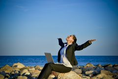 Attractive business woman working on laptop at beach. Attractive business woman working on a laptop sitting on some rocks at the beach looking up to sky thinking Stock Image