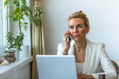 Attractive business woman working on laptop computer and speaks mobile phone. Royalty Free Stock Photography