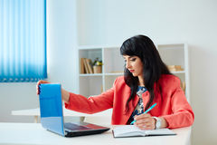 Attractive business woman working at laptop in office. Attractive business woman working at laptop in the office or classroom Stock Images