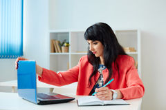 Attractive business woman working at laptop in office. Attractive business woman working at laptop in the office or classroom Royalty Free Stock Photo
