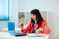 Attractive business woman working at laptop in office. Attractive business woman working at laptop in the office or classroom Stock Photo