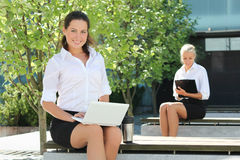 Attractive business women with folder and laptop sitting outside Royalty Free Stock Photo