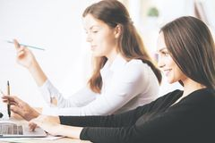 Attractive businessladies using laptop at workplace Royalty Free Stock Image