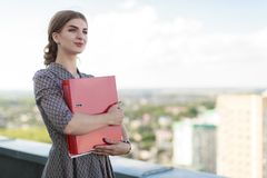 Attractive businesslady in patterned dress stand on the roof and hold paper folder Stock Photography
