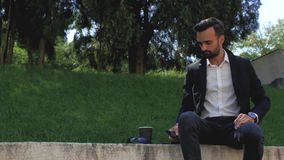 Attractive businessman with a beard in a classic suit sits in a park on a background of grass looks at the phone and drinks tea or. Coffee from a disposable cup stock footage