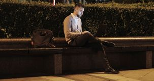 Attractive businessman with a beard sitting on a bench and working on a laptop. stock footage