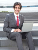Attractive businessman with black hair and computer Stock Photos