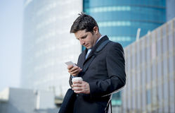 Attractive businessman checking text message on mobile phone outdoors Royalty Free Stock Images