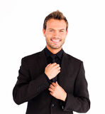Attractive businessman corrects a tie Stock Photography