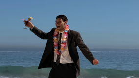Attractive businessman dancing on the beach