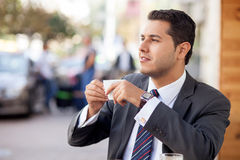 Attractive businessman is enjoying hot drink in Stock Image