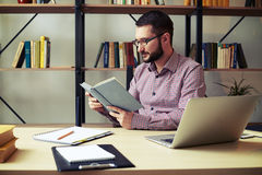 Attractive businessman focused reading book at home office Stock Photography