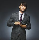 Attractive businessman getting dressed on black background. Portrait of handsome young male model buttoning coat. Attractive businessman getting dressed. Mixed Stock Photos