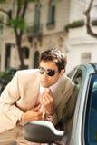 Businessman grooming on car mirror. Stock Image