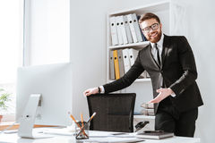 Attractive businessman holding chair. Look at camera. Picture of attractive businessman standing in office while holding chair. Look at camera Stock Images