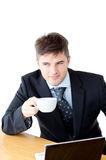 Attractive businessman holding a cup of coffee. In front of his laptop against a white background Royalty Free Stock Photography