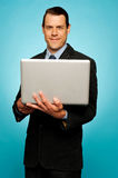 Attractive businessman holding laptop. Attractive smiling businessman holding laptop and surfing web Stock Photos