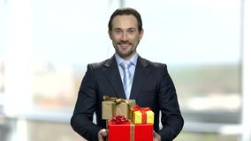 Attractive businessman holding pile of gift boxes.