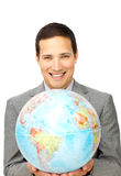 Attractive businessman holding a terrestrial globe Stock Photo