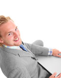Attractive businessman with laptop sitting down Stock Photography