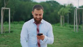 Attractive businessman looking on the mobile phone, feeling happy, seeing good news. stock video footage