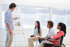Attractive businessman making a presentation to his fellow coworkers Stock Photo