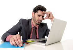 Attractive businessman at office desk working on computer laptop looking tired and busy Stock Photo